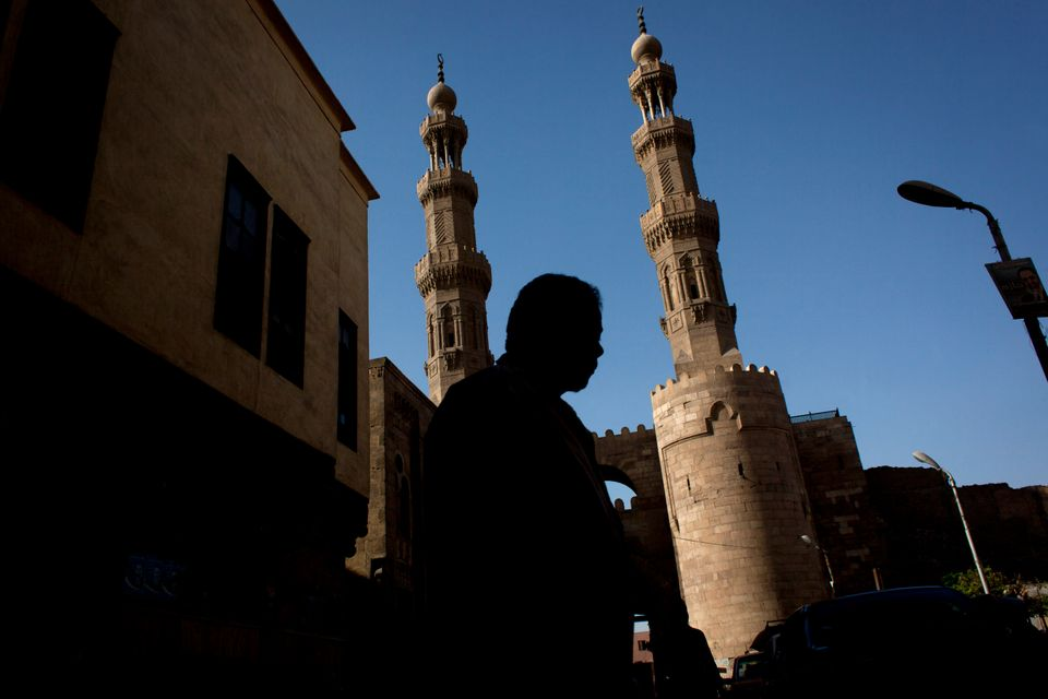In this photo taken Tuesday, May 14, 2013, an Egyptian man passes by the Bab Zuweila, an archway that served as the southern