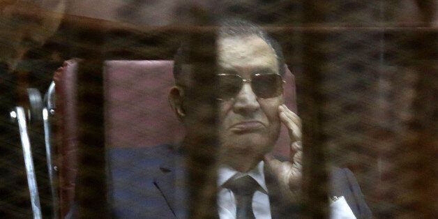 Former Egyptian President Hosni Mubarak, attends with his two sons Gamal Mubarak, and Alaa Mubarak, the verdict in the corrup
