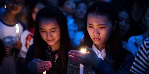 Local residents take part in a candlelight vigil to pay their respect to victims of the sunken ship in Jianli, in China's Hub