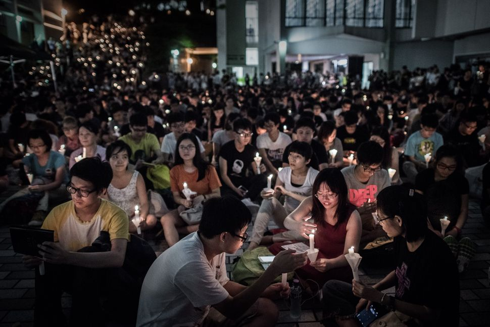 Participants hold candles during a vigil organised by students to commemorate China's 1989 Tiananmen Square crackdown, at the