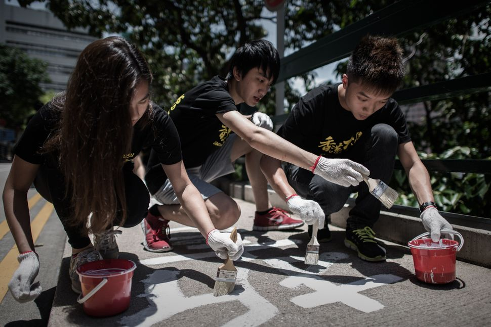 Students re-paint a message of commemoration to China's 1989 Tiananmen Square crackdown, on the campus of Hong Kong Universit