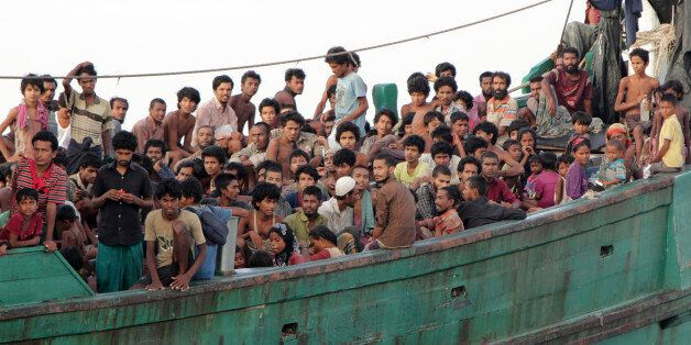 Migrants sit on their boat as they wait to be rescued by Acehnese fishermen on the sea off East Aceh, Indonesia, Wednesday, M