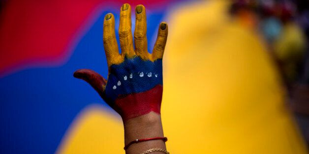 A woman with her hand painted with the colors of the Venezuelan flag attends a rally in support of opposition leader Leopoldo