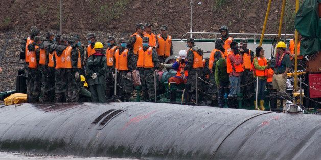 Chinese soldiers stand near a wrapped body as rescuers work on the capsized ship, center, on the Yangtze River in central Chi