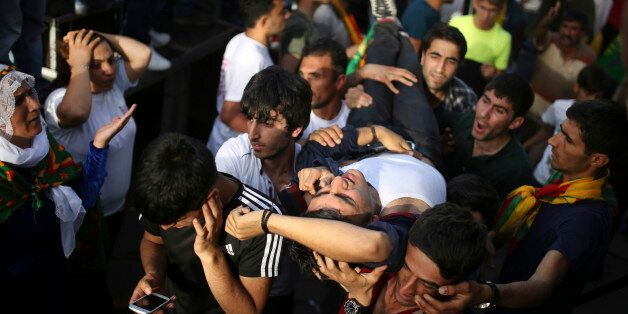 A youth is carried after being wounded in an explosion at a pro-Kurdish People's Democratic Party (DHP) rally in Diyarbakir