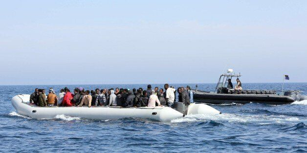 Libyan coast guards escort a boat carrying illegal migrants, who had hoped to set off to Europe with the help of people smugg