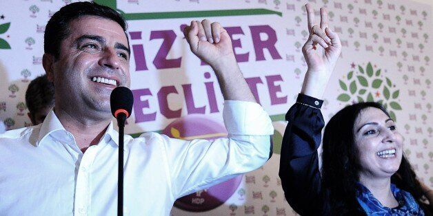 Selahattin Demirtas (L) and Figen Yukseldag (R), co-chairs of the pro-Kurdish Peoples' Democratic Party (HDP), gesture during