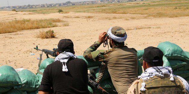 Iraqi Kurdish Peshmerga forces and al-Hashd al-Shaabi factions hold a position close to the village of Bashir in the Qatqa Da