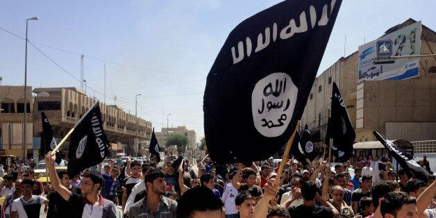 FILE - In this June 16, 2014 file photo, demonstrators chant pro-Islamic State group, slogans as they carry the group's flags