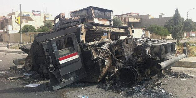 FILE - In this Thursday, June 12, 2014 file photo, an Iraqi army armored vehicle is seen burned on a street of the northern c