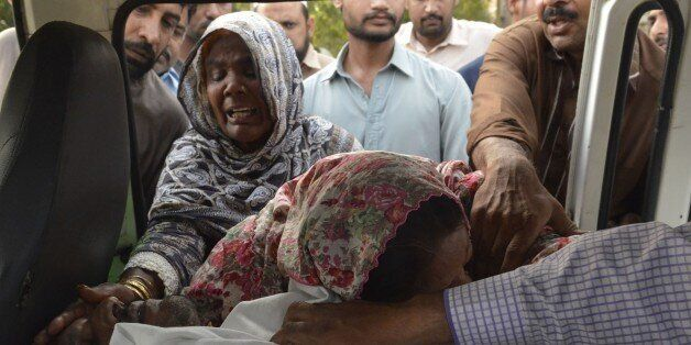 Pakistani Christian relatives of convicted murderer Aftab Bahadur Masih mourn beside his body after his execution in Lahore o