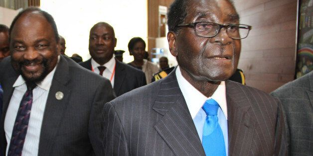 Zimbabwe's President Robert Mugabe, right, arrives for the heads of state meeting of the annual African Union (AU) summit, he
