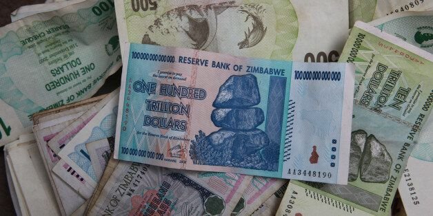 An  old one hundred trillion Zimbabwean dollar note on top of a pile of other old Zimbabwean notes of various denominations