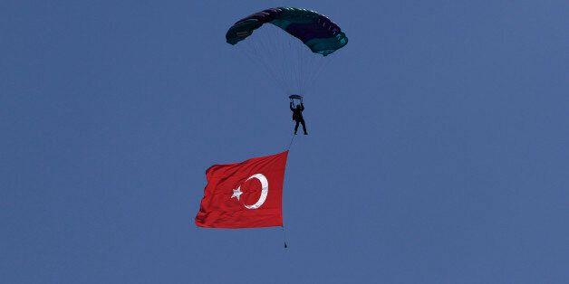 A Turkish parachutist with a Turkish flag flies over a military parade in the Turkish occupied area of the divided capital Ni