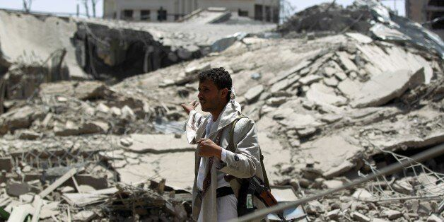 A Yemeni man stands near a collapsed building following an air-strike by the Saudi-led coalition in the capital Sanaa on June