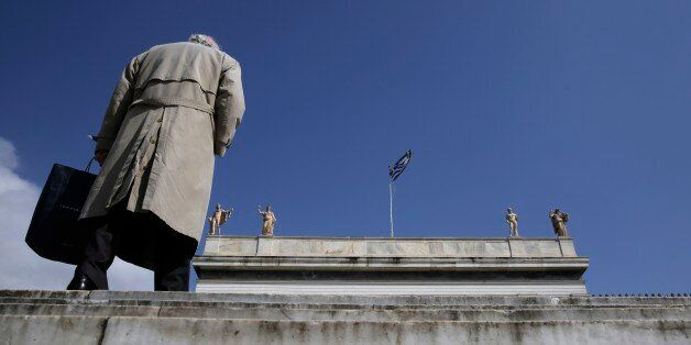 A pedestrian walks past statues, which stand at the top of the National Archaeological Museum of Greece as a Greek flag flies