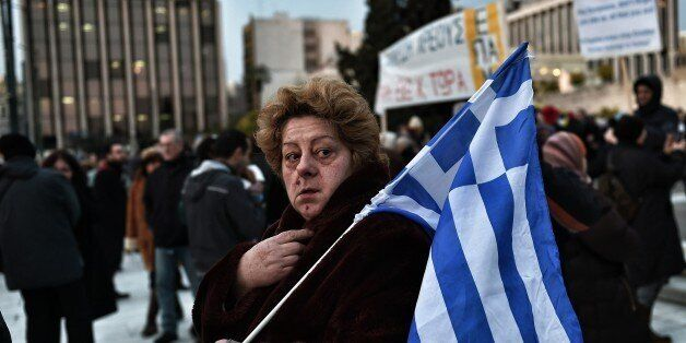 A woman holds a Greek flag as people demonstrate in front of the parliament to support the Greek government in Athens on Febr