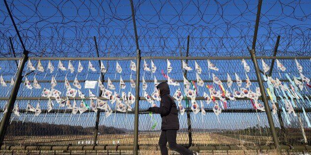 A South Korean tourist walks along a military barbed wire fence decorated with national flags at the Imjingak peace park at t