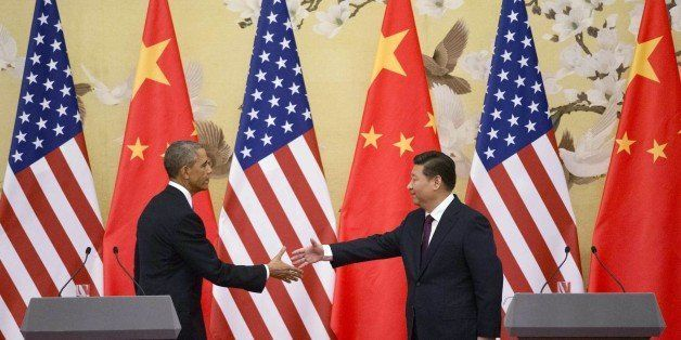 US President Barack Obama (L) and China's President Xi Jinping reach out to shake hands following a bilateral meeting  at the