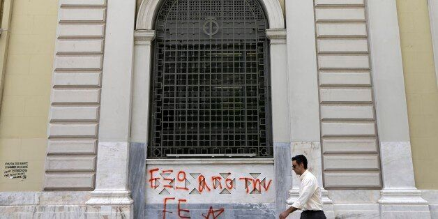 A pedestrian passes a sign reads ''Out of EU (European Union)'' at the headquarters of National Bank of Greece in Athens, Wed