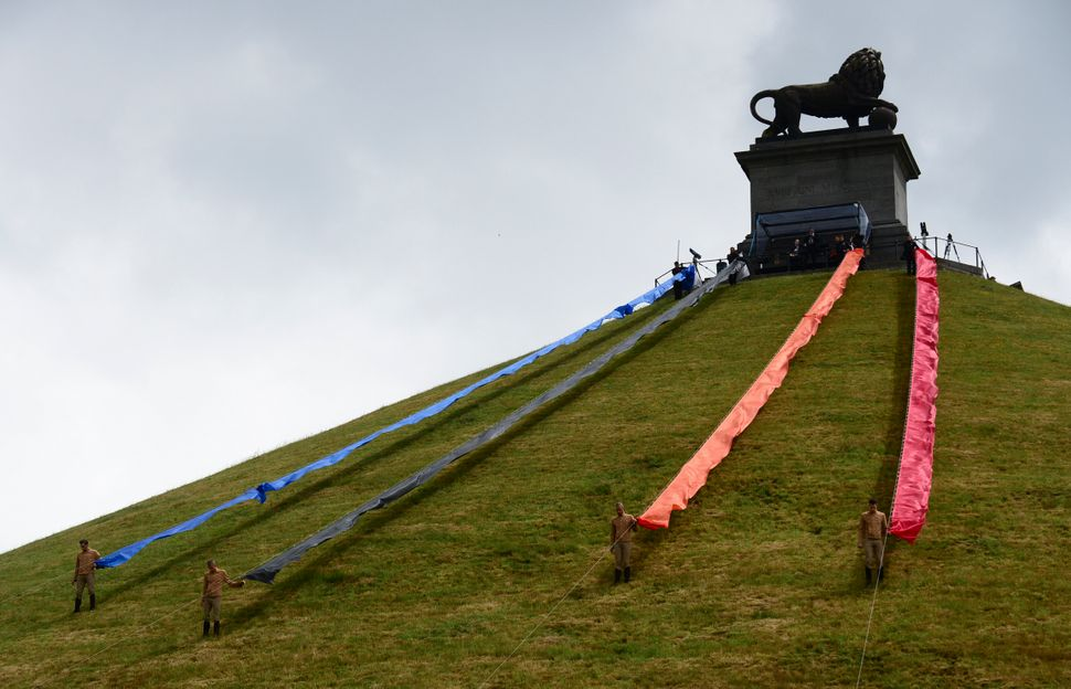 Soldiers pull ribbons down from the Lion's Mound during a ceremony to commemorate the bicentenary of the Battle of Waterloo i
