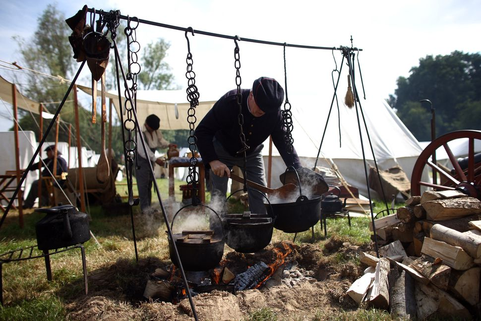 A man prepares food in a re-enactment of the Battle of Waterloo in Braine l'Alleud, Belgium, on June 18, 2015.