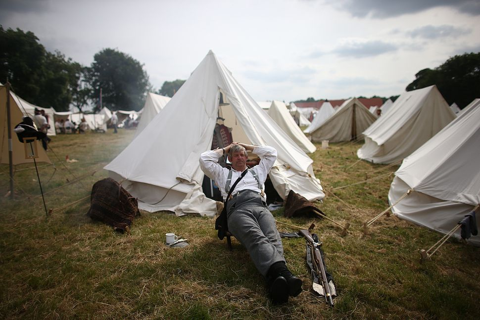 A man rests in the camp in a re-enactment of the Battle of Waterloo in Braine l'Alleud, Belgium, on June 18, 2015.