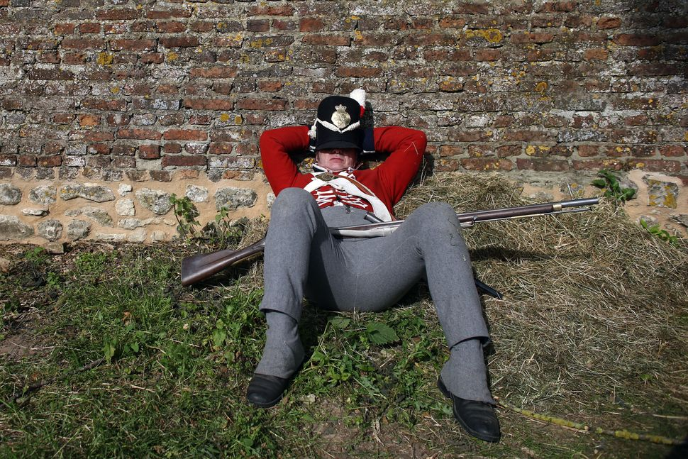A man dressed as a British soldier rests in a re-enactment of the Battle of Waterloo in Braine l'Alleud, Belgium, on June 18,
