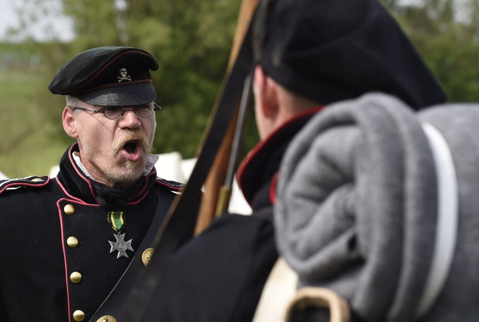 A re-enactor dressed as a Prussian soldier gives orders in a re-enactment of the Battle of Waterloo in Braine l'Alleud, Belgi