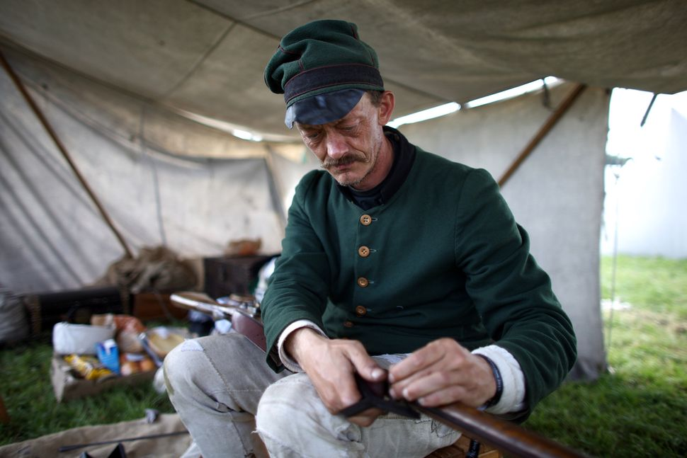 A man cleans a prop rifle in a re-enactment of the Battle of Waterloo in Braine l'Alleud, Belgium, on June 18, 2015.