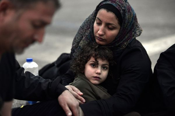 A Syrian mother warms up her daughter after arriving at Lesbos on June 18, 2015.