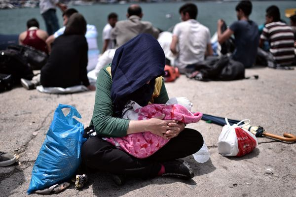 An Afghan migrant holds her two-month-old baby in Lesbos, after having walked for two days from a northern part of the island