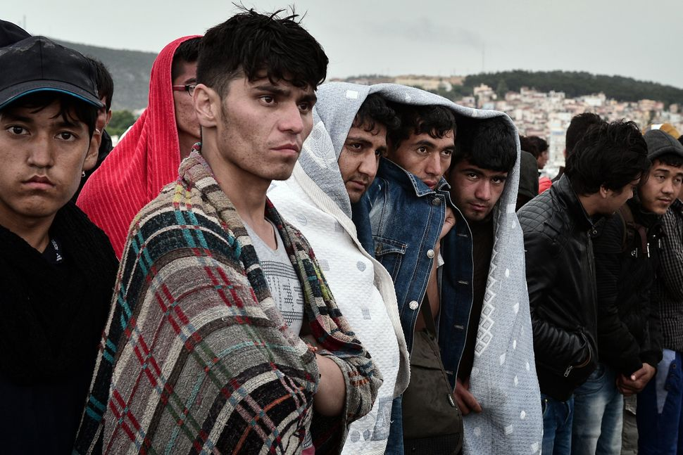 Migrants protect themselves from the rain while waiting to be registered in Lesbos on June 19, 2015.