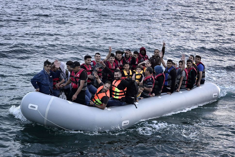 Syrian refugees flash the victory as their dinghy arrives at Lesbos on June 18, 2015.