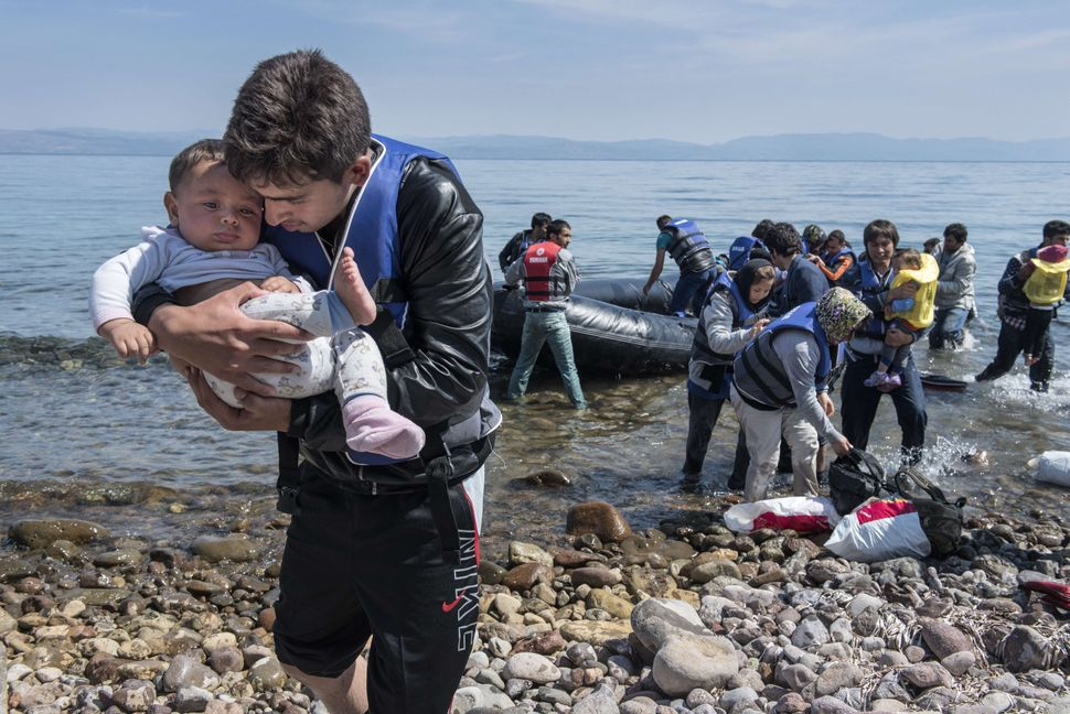 An Afghan refugee carries a baby upon arrival at Lesbos on June 2, 2015.