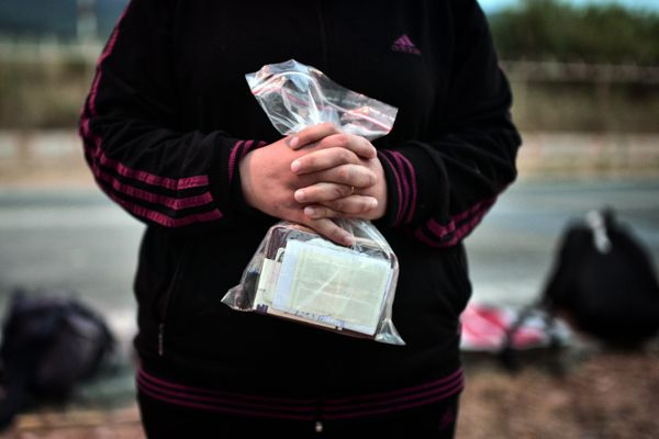 A Syrian migrant holds her family's documents after disembarking at Lesbos on June 18, 2015.