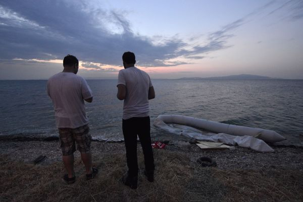 Syrian refugees attempt to send messages on their cell phones upon arrival at Lesbos on June 18, 2015.