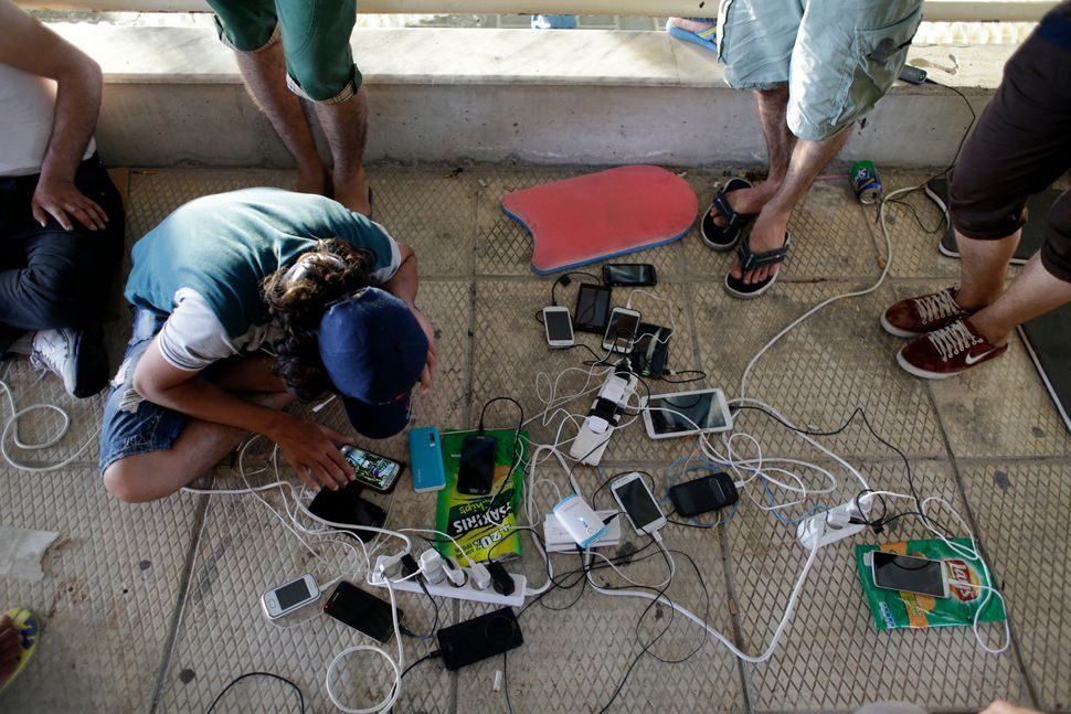 Syrian migrants wait by a makeshift cell phone charging station at an old indoor swimming pool in Lesbos, on June 16, 2015.