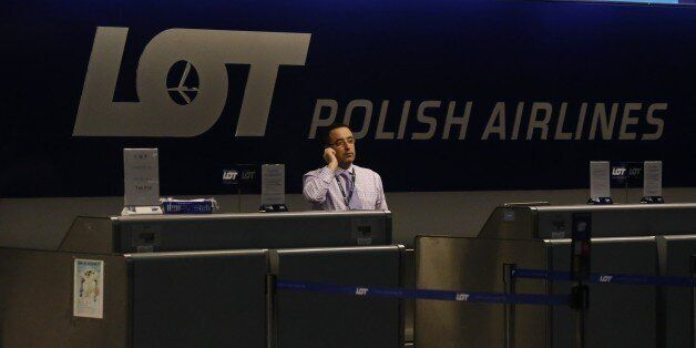 A Polish Airlines employee talks on the phone in a darkened ticket counter waiting for flight 003 from Warsaw, a Boeing 787 a