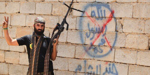 A heavily armed Iraqi Shiite fighter from the Popular Mobilisation units flashes the V for victory sign in front of graffiti