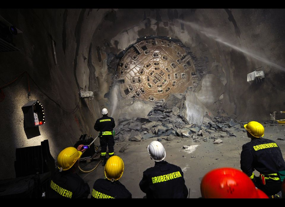 A giant drilling machine, nicknamed 'Sissi,' drills through the last bit of rock as miners look on.