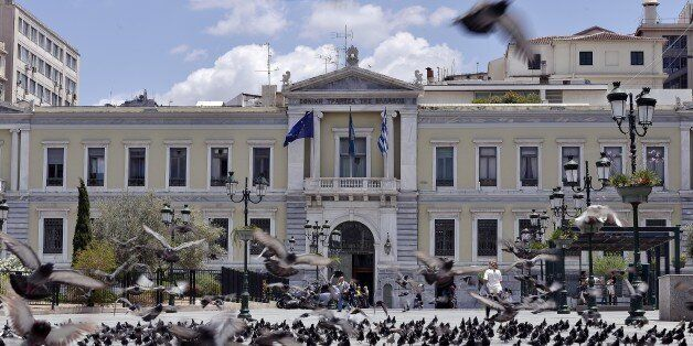 Pigeons fly in front of the National Bank of Greece headquarters in central Athens on June 23, 2015. Hopes that Greece and it