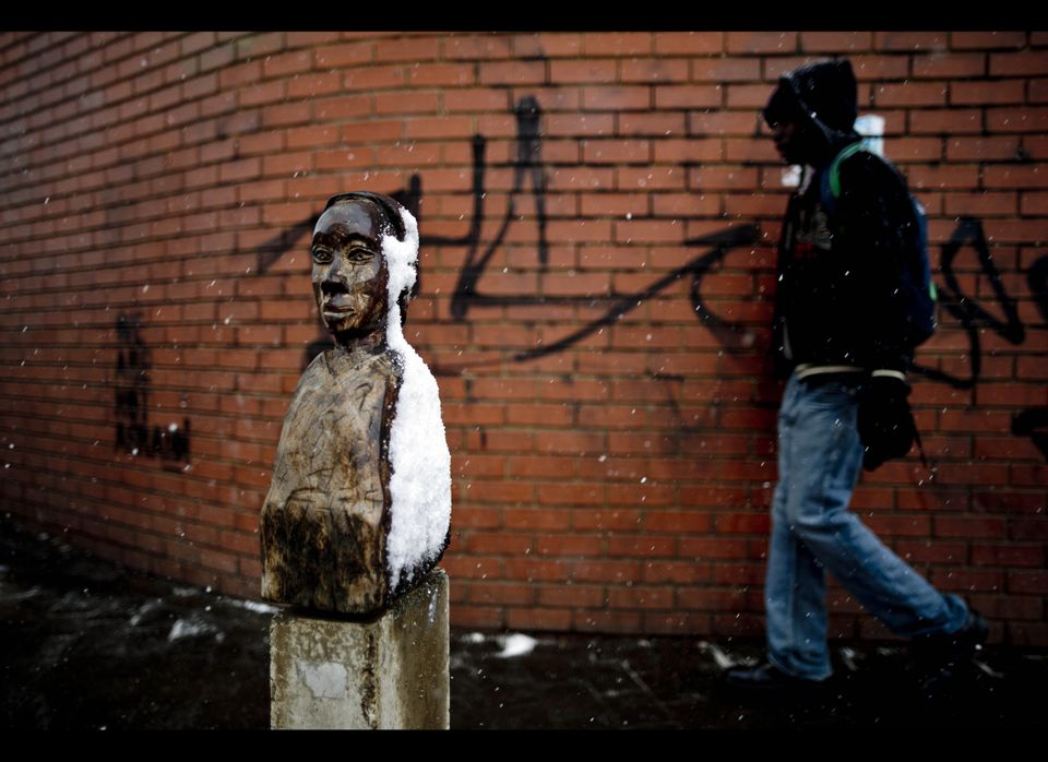 A man walks past a statue covered in snow on August 7, 2012 in Johannesburg. Snow falls annually in the mountains of South Af