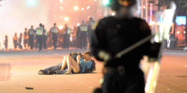 VANCOUVER, BC - JUNE 15:  Riot police walk in the street as a couple kiss on June 15, 2011 in Vancouver, Canada. Vancouver br