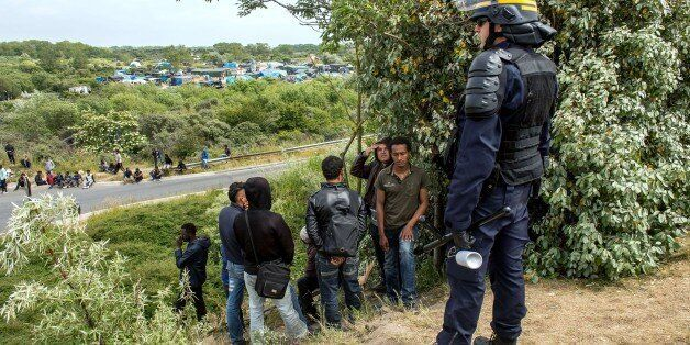A French riot police officer (CRS) stands in front of men on the side of the road as illegal migrants attempt to hide in lorr