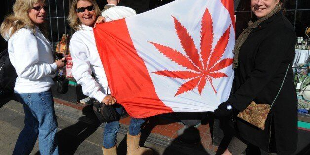 Visitors pose in front of a flag similiar to the Canadian one but showing a cannabis plant instead of a maple leaf at a store