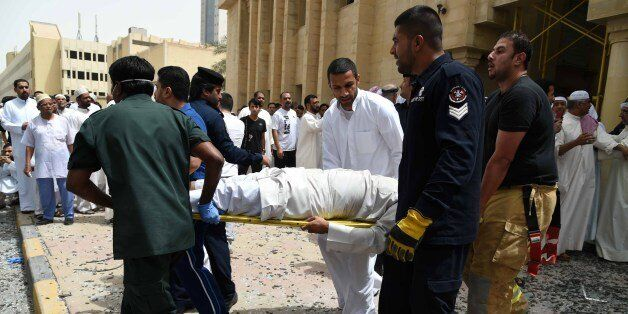 Kuwaiti security personnel and medical staff carry a man on a stretcher at the site of a suicide bombing that targeted the Sh