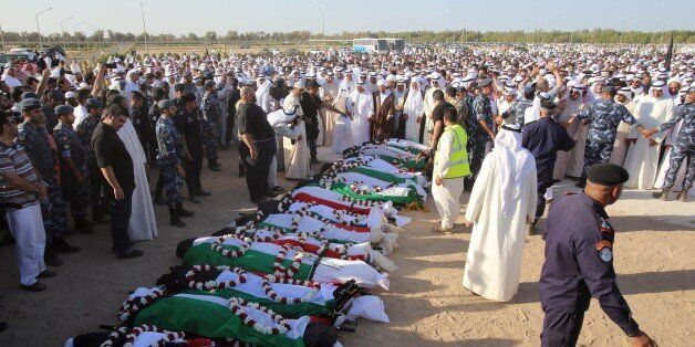 Mourners pray over the bodies of the victims of the Al-Imam Al-Sadeq mosque bombing, during a mass funeral at Jaafari cemeter