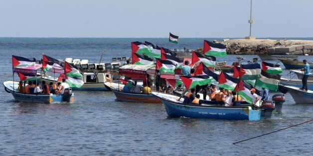 Palestinians hold their national flag as they ride boats during a rally to show support for activists aboard a flotilla of bo