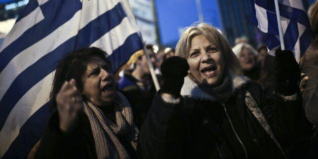People shout slogans and wave Greek flags during an anti-austerity, pro-government rally in front of the Greek Parliament in